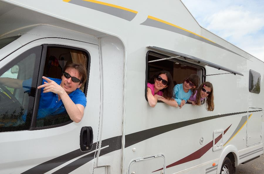 A family leaning out the windows of a RV