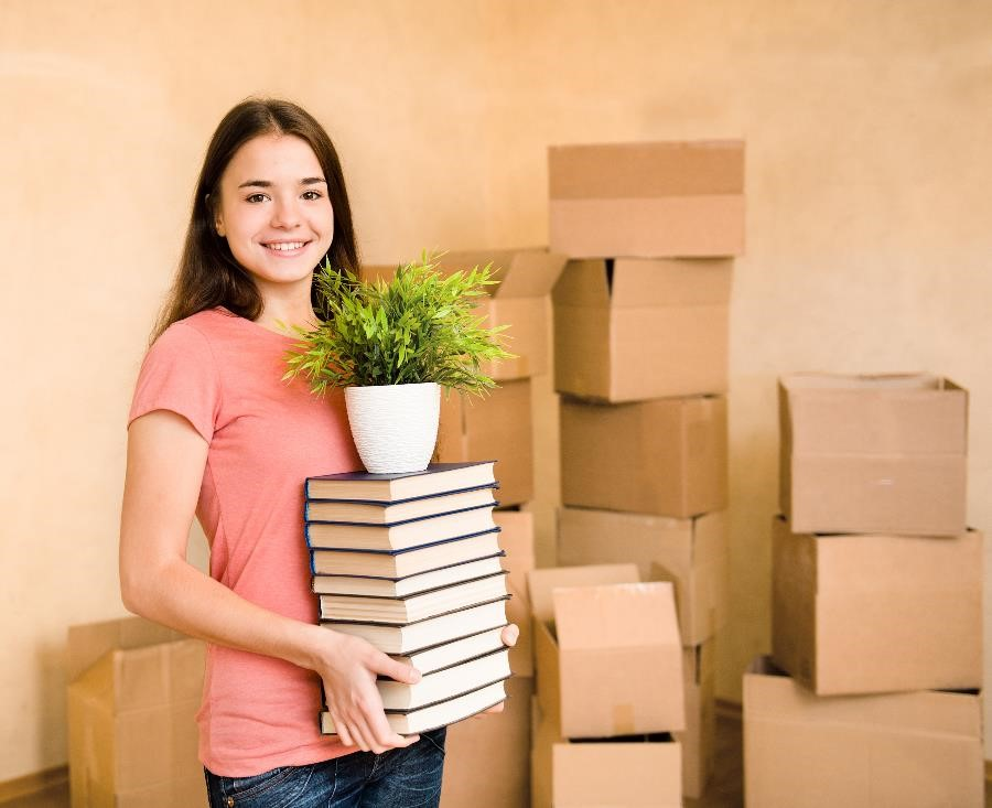 Girl holding stack of books with boxes behind her