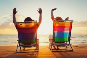 Two adults in colorful beach chairs raising arms in excitement