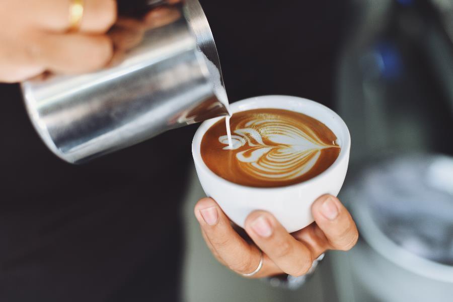Barista pouring coffee creamer into a cup to make a pretty design.