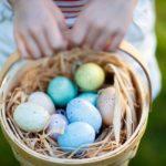 child holding basket full of colorful eggs