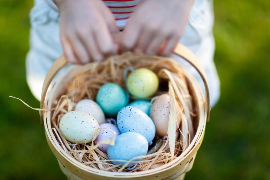 child holding basket full of colorful eggs