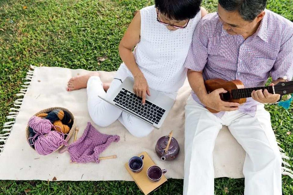 an older couple outside, sitting on a blanket, with a computer, ukelele, tea cups, and a bowl of yarn