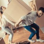A couple struggles to move a box