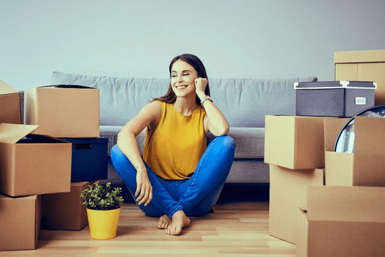A woman sitting on the floor next to many boxes