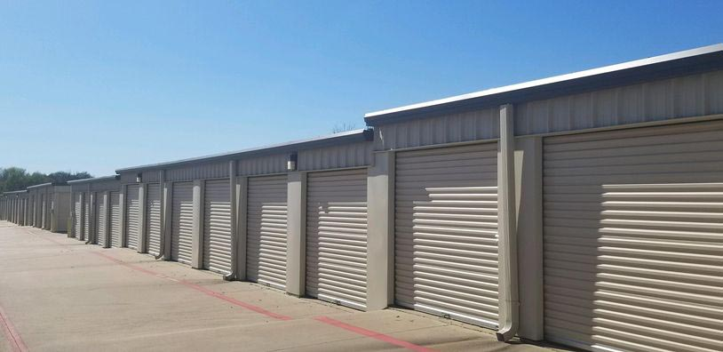 A row of outdoor storage units with large white doors in a clean area