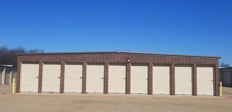A row of small, outdoor storage units with white doors
