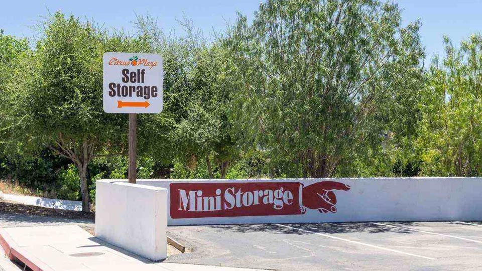 A parking lot with a sign pointing to Citrus Plaza Self Storage