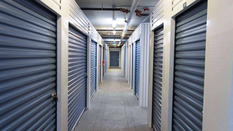 A clean, well-lit hallway of indoor storage units with blue doors