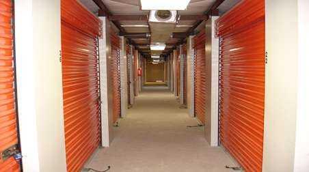 Indoor storage units with large, orange doors and secure locks