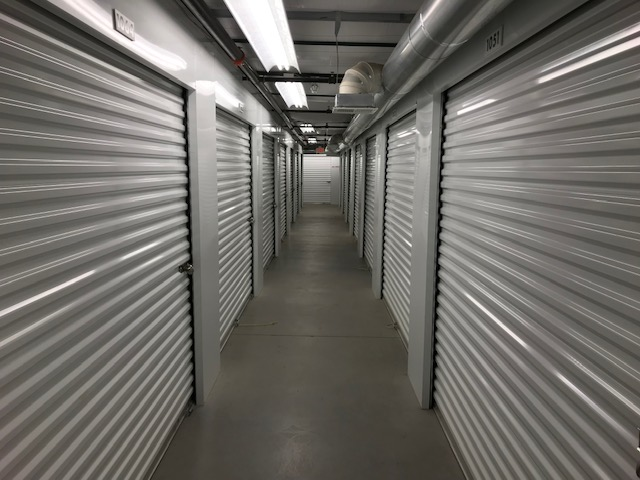 A well-lit and clean hallway of indoor storage units with white doors