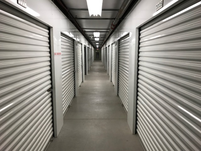 A well-lit hallway of large indoor storage units with white doors