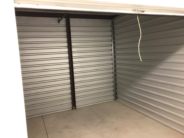 A view inside an outdoor storage unit that is empty and clean
