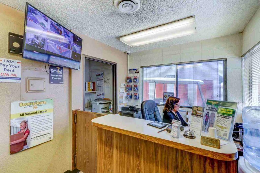 Inside storage facility front office overlooking the front desk with a television monitoring security