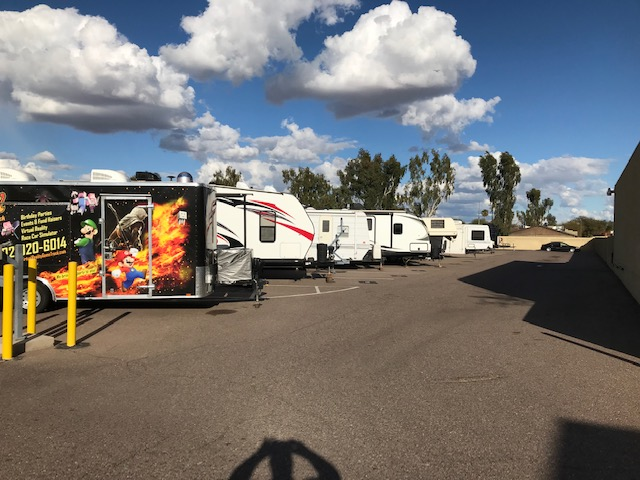 An outdoor parking lot with RVs and trailers parked next to each other