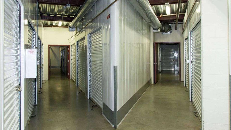 Inside a self storage facility with rows of indoor units in clean, well-lit hallways