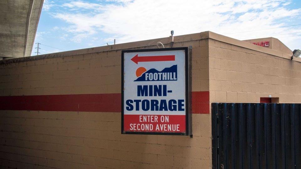 Exterior signage for Foothill Mini Storage with an arrow to the entrance