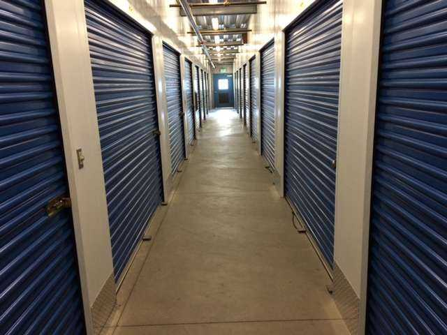 A well lit hallway of large indoor storage units with blue doors