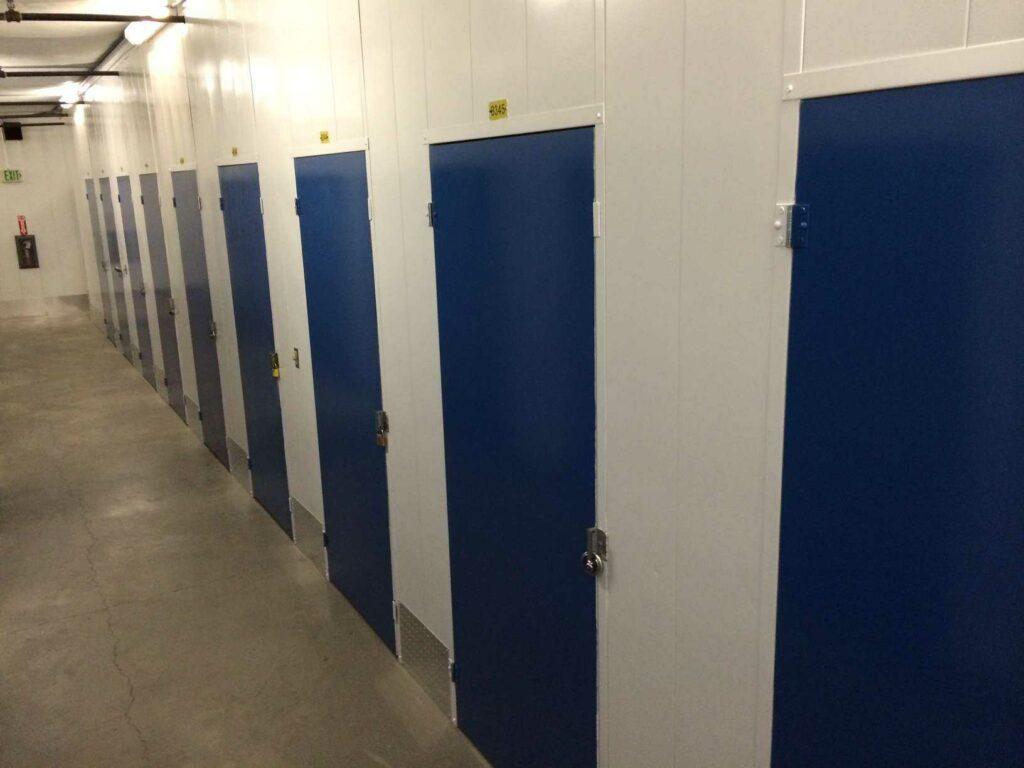A clean, well-lit hallway of indoor storage lockers with blue doors