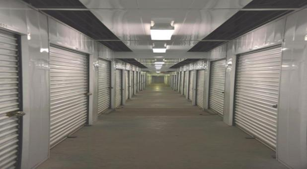 A long row of large indoor storage units with white doors in a well lit hallway