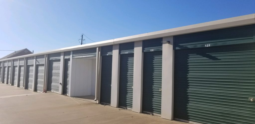 A row of small and large outdoor storage units with green doors