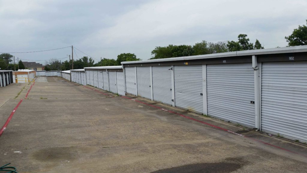 A long row out large outdoor storage units with white doors