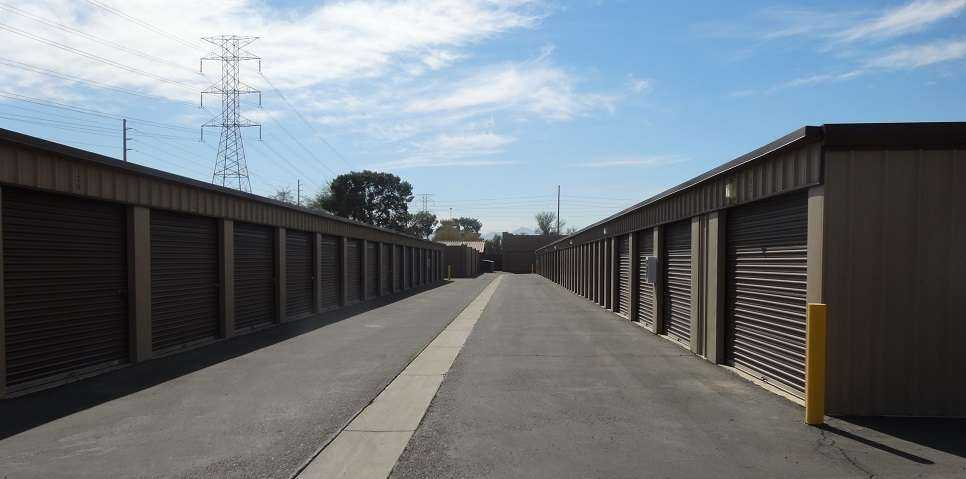 A long row of large outdoor storage units with red doors