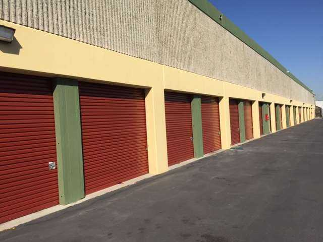 Row of large outdoor storage units with red doors in a clean area