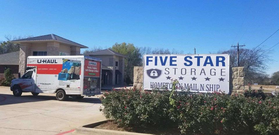 Five Star Storage signage in front of facility with a U-Haul parked in front of the facility