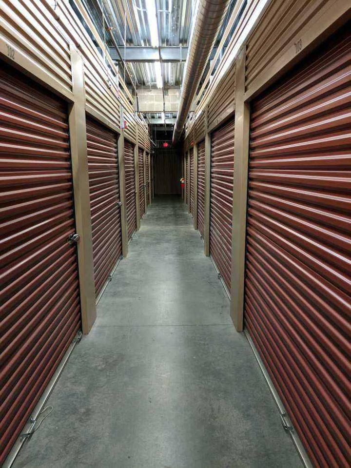 Clean hallway of large indoor storage units with red doors