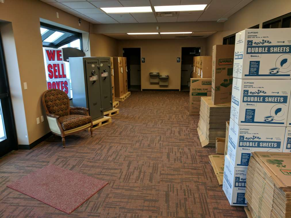 Indoor office area with moving boxes for sale and a rest area