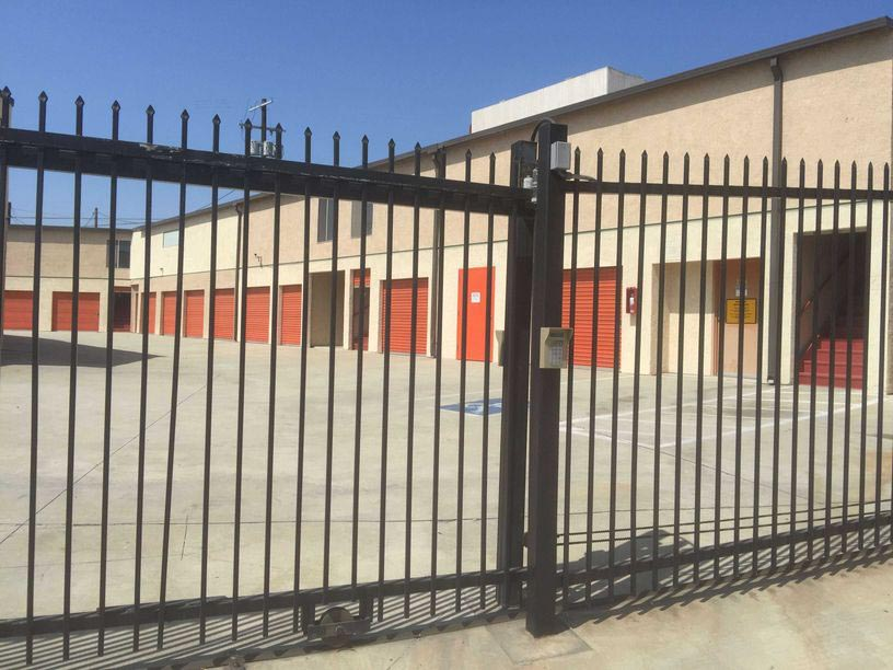 View of gate going into an area of outdoor storage units with orange doors