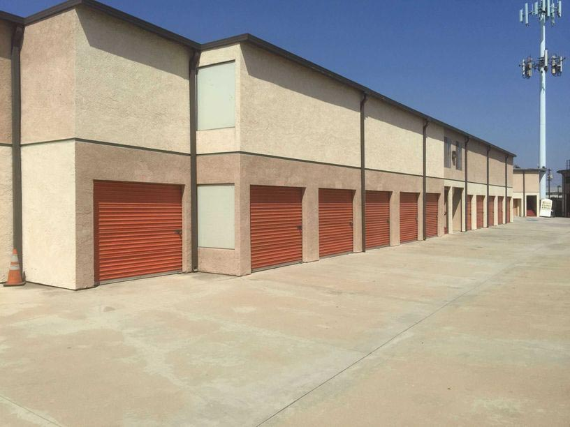 A row of large outdoor storage units with red doors