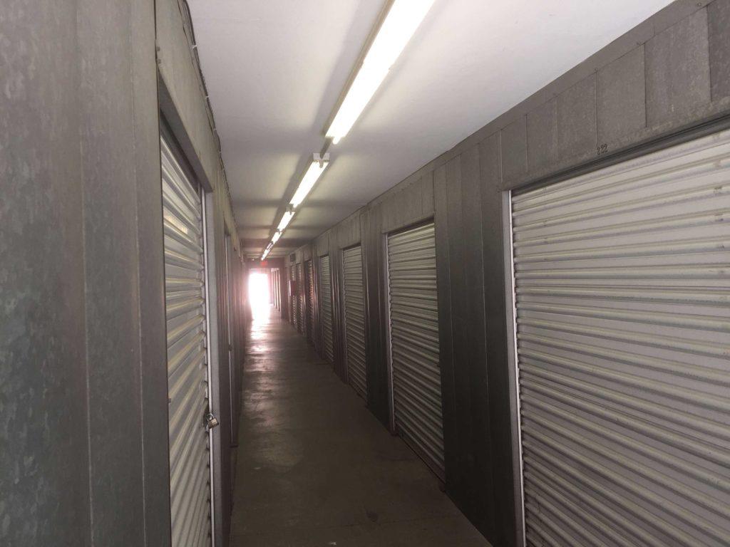 Indoor hallway of storage units with grey doors and secure locks