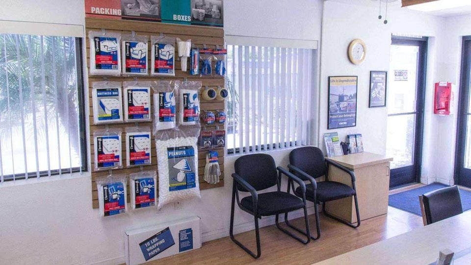 Inside a facility office with packing and moving supplies on display with a seating area next to it