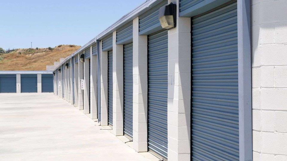 Row of outdoor storage units with large blue doors in a clean area