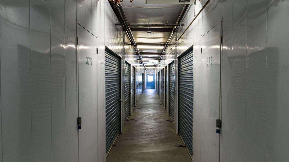 A hallway of large indoor storage units with blue doors