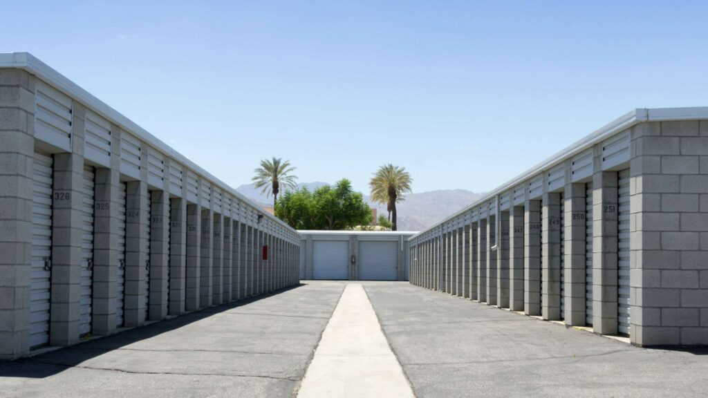 Row of outdoor storage units with white doors in a clear area