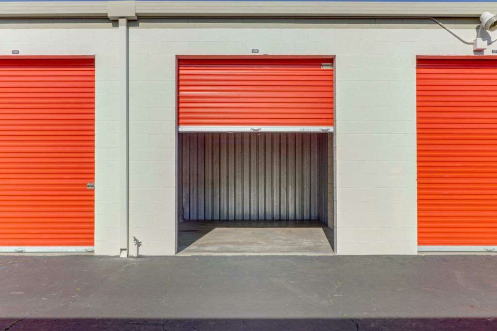 Outdoor storage units with large orange doors with one door open to a clean, empty unit