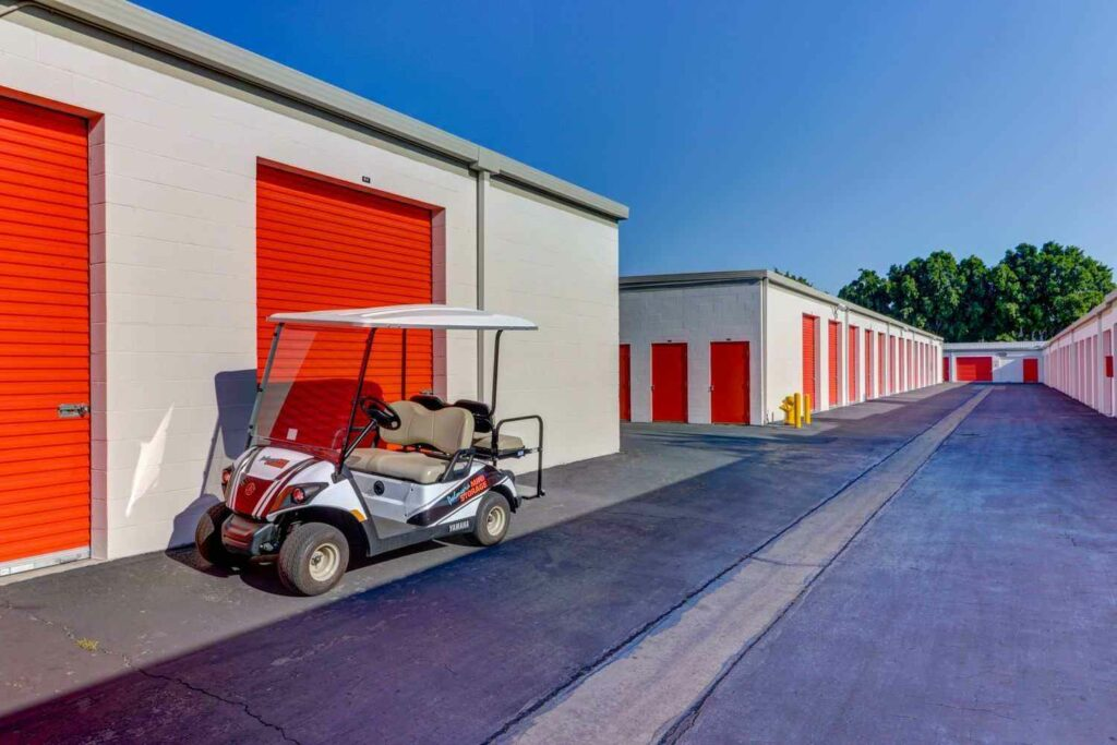 A long row of large outdoor storage units with orange doors in a clean area