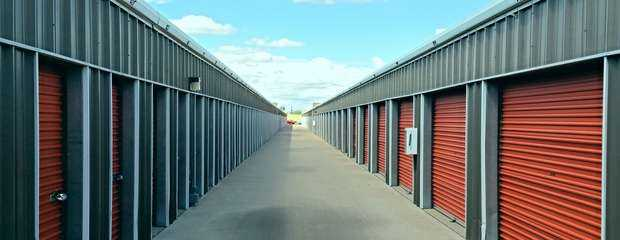 A long row of large and small outdoor storage units in a clean area
