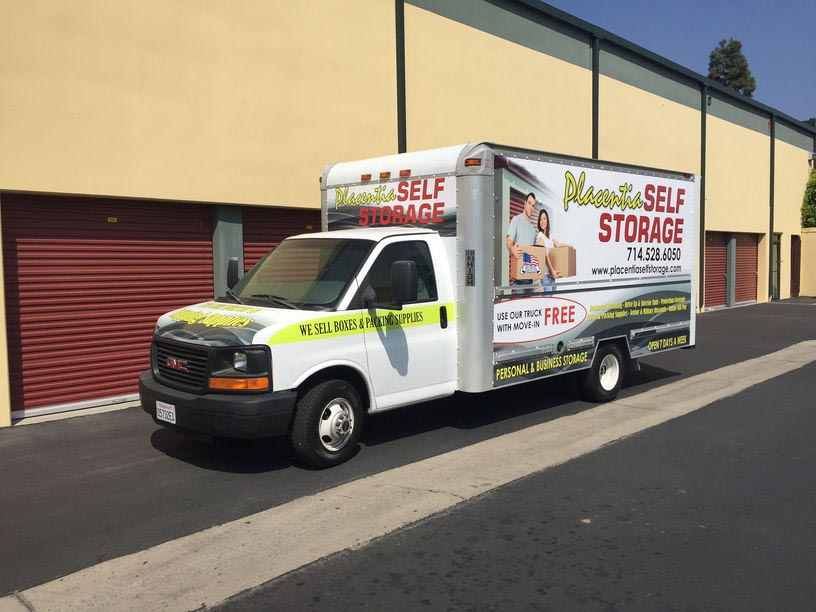 A Placentia Self Storage moving truck parked outside of outdoor storage units