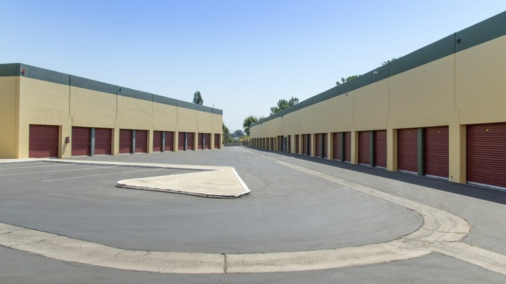 An outdoor area of large storage units with parking and a long driveway