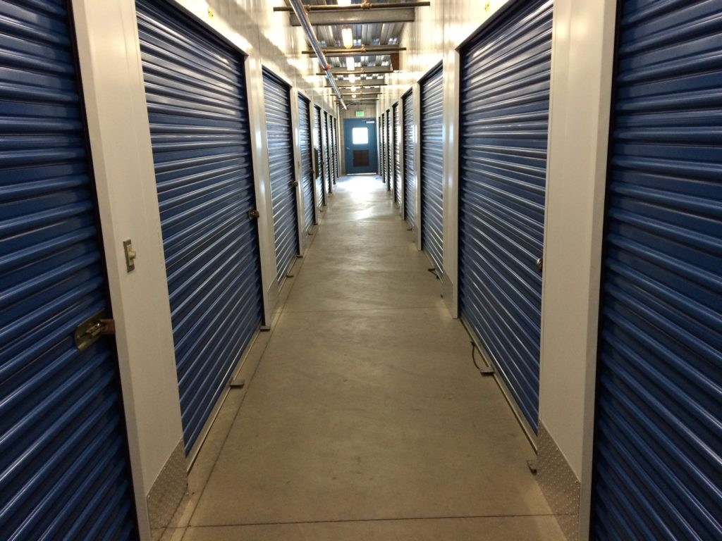 A well-lit hallway of large indoor storage units with blue doors