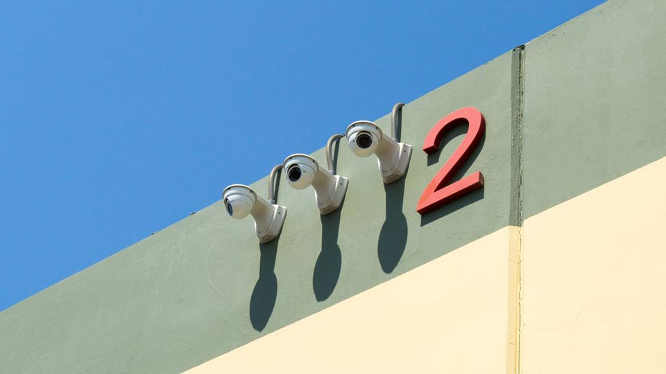 Exterior surveillance cameras on the side of facility building