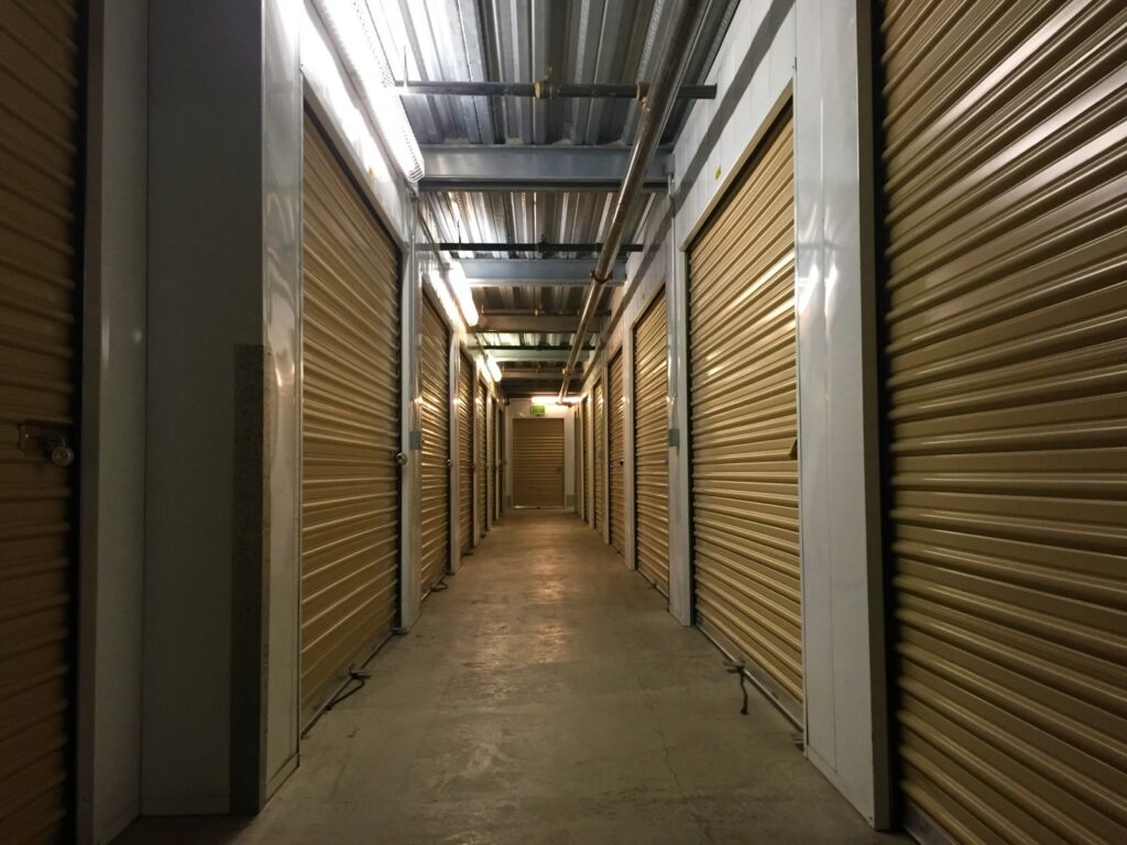 Indoor storage units with large, yellow doors in a well-lit hallway