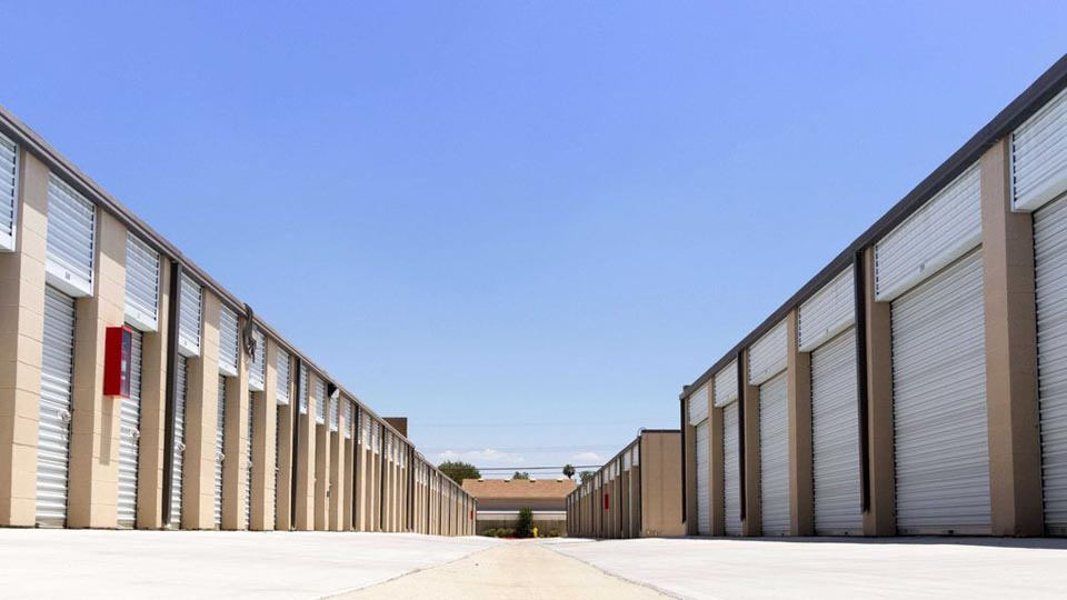 A long row of large outdoor storage units with white doors in a clean area