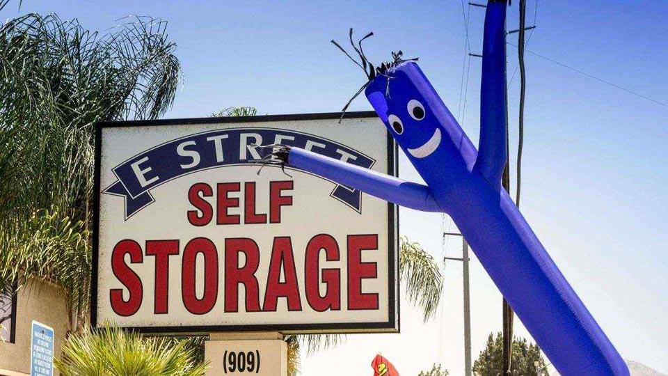 Street signage for E Street Self Storage with an inflatable by the sign