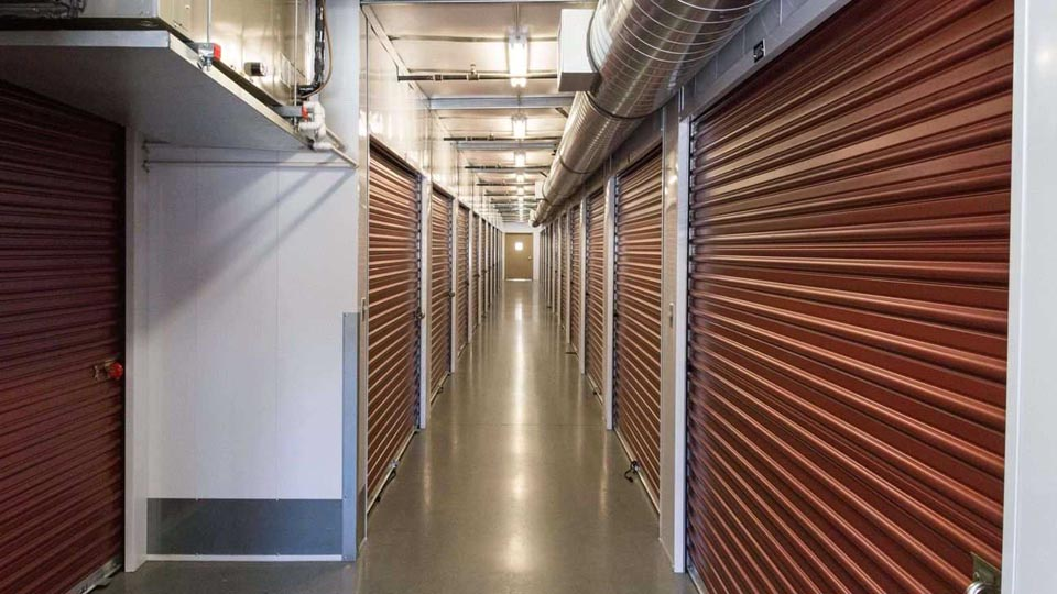 A long row of large indoor storage units with red doors in a well-lit and clean hallway