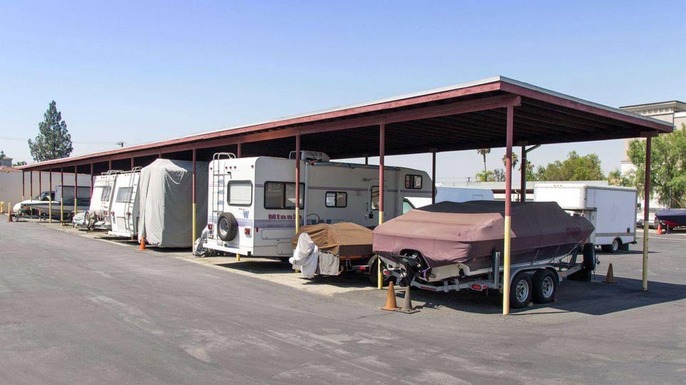 Covered outdoor parking with RVs and boats parked underneath